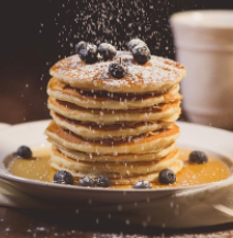 Stack of blueberry pancakes with powdered sugar